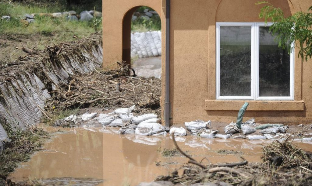 mud overpowering sandbags around a home