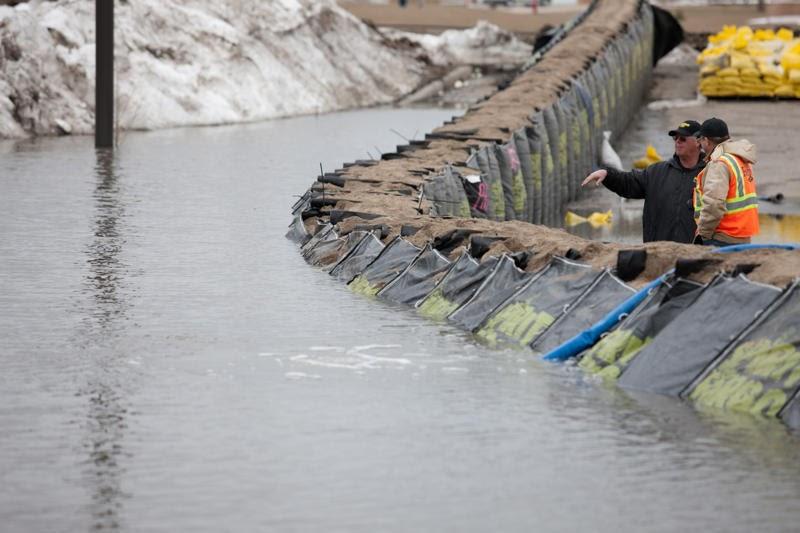Responders talking behind functioning TrapBag flood barrier